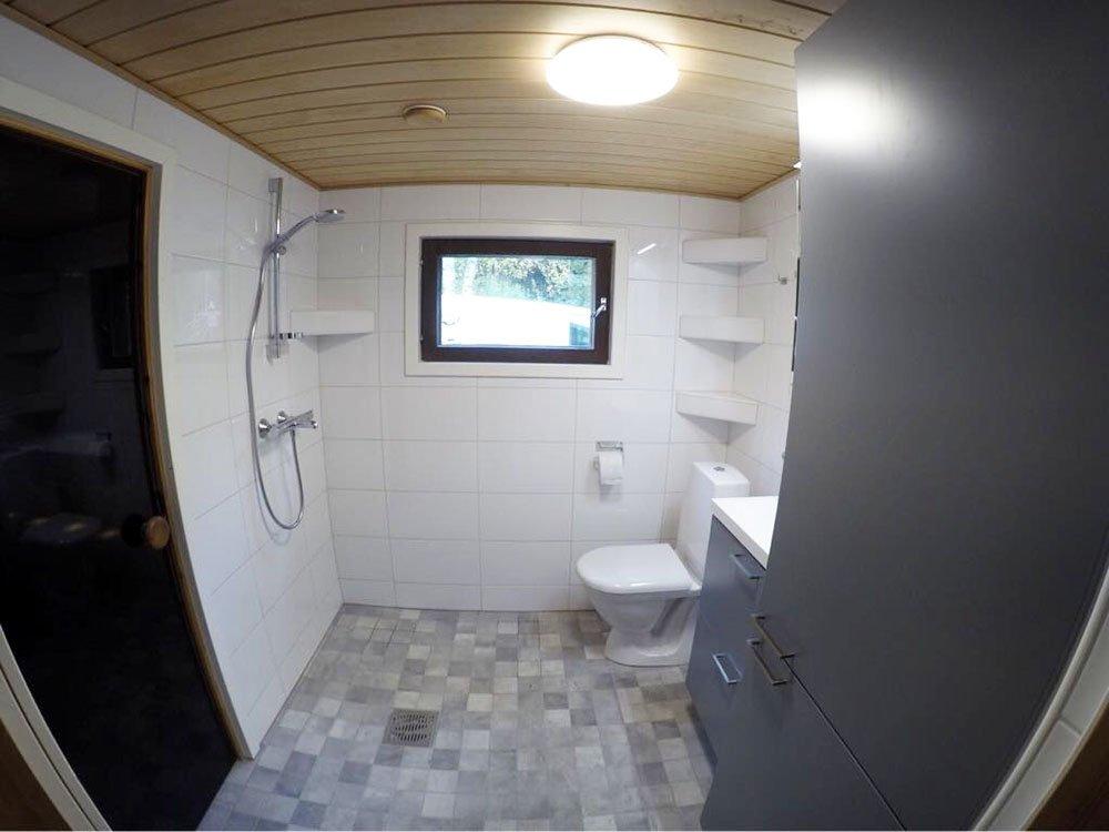 Vapaa-ajan asunnon kylpyhuone, johon haluttiin lisää säilytystilaa sekä lämminvesivaraaja sekä pumppu katseilta piiloon